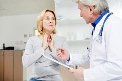 Symptoms of flu. Sick mid-aged female complaining about sore throat to her doctor Stock Photos