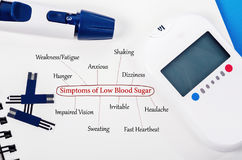 Symptoms of low blood sugar. Symptoms of low blood sugar with blood glucose meter and equipment on book background Royalty Free Stock Photos