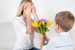 Synów chwyty za jego bukietem piękni kwiaty dla jego ukochany matki Pojęcie świętowanie, kobiety ` s dzień zdjęcie stock