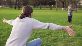 Synów bieg w macierzystego ` s otwierają ręki i ściskają ona w wiosna parku zdjęcie wideo