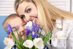 Syn daje jego ukochany matce pięknemu bukietowi tulipany Pojęcie świętowanie, kobiety ` s dzień obrazy royalty free