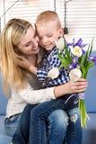 Syn daje jego ukochany matce pięknemu bukietowi tulipany Pojęcie świętowanie, kobiety ` s dzień obraz royalty free