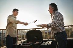 Syn daje kiełbasie jego ojciec nad grillem Fotografia Stock