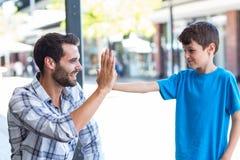 Syn i ojciec robi wysokości pięć zdjęcie stock