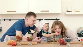 Syn taktuje jego rodziców z truskawkami Przygotowywają owocowej sałatki w kuchni zbiory