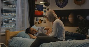 Syn wpólnie i matka przy wezgłowiem zdjęcie wideo
