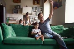Syn z ojca dopatrywania piłką nożną na TV wpólnie fotografia stock