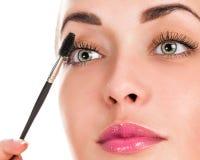 Syna Makeup Applicera mascara på snärtarna Royaltyfri Foto