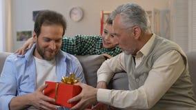 Syna przymknięcie ojcuje oczy, dziadek daje prezenta pudełko, urodzinowa niespodzianka, rodzina zbiory wideo