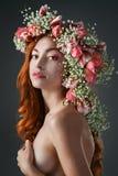 Synad rödhårig manflicka med ljus makeup och en krans av vårflöde fotografering för bildbyråer