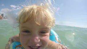 Synade små blonda blått behandla som ett barn flickan som spelar i vattenvideoen arkivfilmer