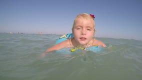 Synade små blonda blått behandla som ett barn flickan som spelar i vattenvideoen lager videofilmer