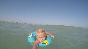 Synade små blonda blått behandla som ett barn flickan som spelar i vattenvideoen stock video