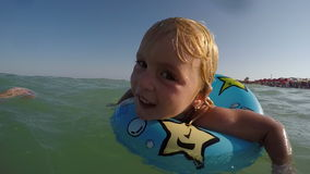 Synade små blonda blått behandla som ett barn flickan som spelar i vattnet med en blå simningcirkelvideo arkivfilmer