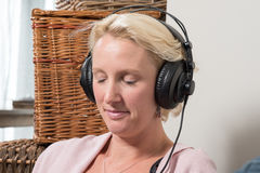 Synar ler den blonda kvinnan för sammanträde i hörlurarslut och arkivfoto