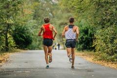 Synchroner Betrieb von zwei jungen Läufern in Herbst Park stockbilder