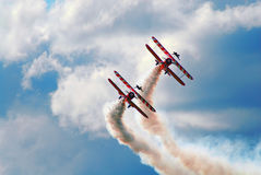 Synchronised flying. 2 vintage aircrafts with wing walkers on the top, in sync with acrobatics Stock Images