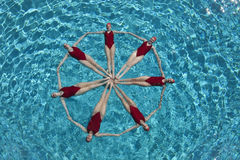 Synchronised Swimmers Forming A Circle. Elevated view of synchronised swimmers forming a circle in pool Royalty Free Stock Images