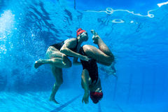 Synchronized Girls Underwater Photo Dance. Synchronized swimming under water photo image of girls pair women finalists about to perform a final practice dance Royalty Free Stock Photo