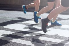 Synchronized legs of marathon runners. Closeup view of synchronized marathon runners feet and legs with motion blur running in the light of the morning on city Royalty Free Stock Photo