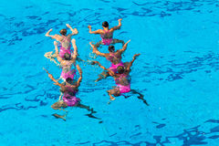 Synchronized Dance Girls Underwater. Girls woman grouped submerged performing their dance routine grouped in two lines under the blue water surface.Costume dress Stock Photography