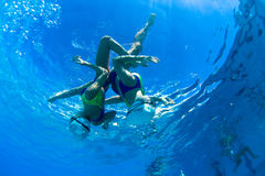 Synchronized Swim Girls Underwater Dance. Synchronized swimming under water photo image of girls pair finalists doing  final practice dance routine upside down Royalty Free Stock Photography
