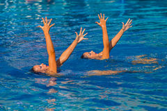 Synchronized Swim Hands Pose. Photo image looking down on girls team performing their dance routine in the water with two girls in the color horizontal frame Stock Photo