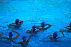 Synchronized swim team practicing. Teenage girls synchronized swim team practicing in bright blue swimming pool water Stock Images