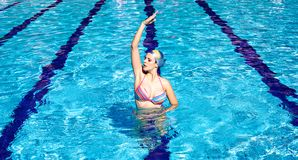 Synchronized swimmer in pool exercizing. Perfect athlete trying sync swimming in pool Stock Photo
