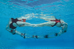 Synchronized Swimmers Forming A Circle. Underwater view of synchronized swimmers forming a circle in pool Royalty Free Stock Photography