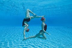 Synchronized Swimmers Performing Underwater. Full length side view of two synchronized swimmers performing underwater Royalty Free Stock Images