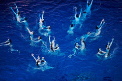Synchronized swimmers team performs Stock Photo