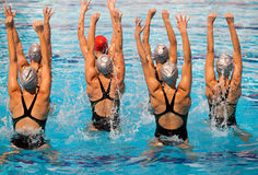 Synchronized swimming. Is a hybrid form of swimming, dance and gymnastics, consisting of swimmers performing a synchronized routine of elaborate moves in the Stock Image