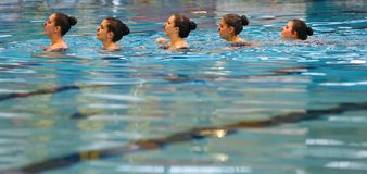 Synchronized swimming team practice detail listening to coach stock images