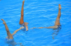 Synchronized swimming. Three  girls synchronized swimming team performing Stock Photo