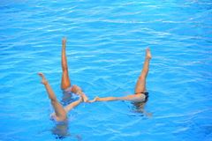 Synchronized swimming. Three  synchronized swimmers legs point up out of the water action Royalty Free Stock Photos