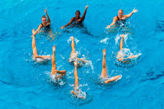 Synchronized Girls Pool Dance. Girls womens team performing their dance routine in the water with three girls in the color horizontal frame doing their dance Royalty Free Stock Photography
