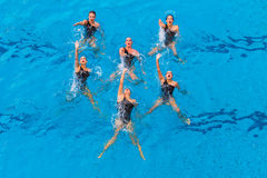 Synchronized Women Six Dance. Six girls women grouped  performing their dance routine onto their backs in the blue water  color horizontal frame doing their Royalty Free Stock Photo