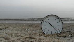 Synchronizuje pojęcia tło, Białe Ściennego zegaru w czerni strzała Na piasek plaży morza oceanie zbiory