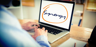 Synergy against businessman working on his laptop. The word synergy against businessman working on his laptop Royalty Free Stock Image
