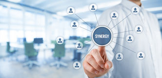 Synergy concept. Synergy opportunity concept. Manager (businessman) click on button with text synergy, cooperating team connected to this button Royalty Free Stock Photography