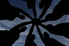 synergy Os trabalhos de equipa juntam-se ao conceito do apoio das mãos junto Céu nocturno Fotografia de Stock Royalty Free