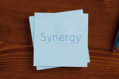 Synergy written on a note Stock Photography