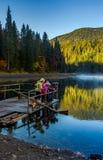 Synevyr湖的游人喂养从木筏的鱼 免版税库存图片
