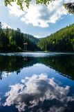 Synevyr lake on summer evening. Beautiful scenery among the forest. reflection of a cloud in a rippled water surface Stock Image