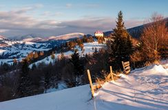 Beautiful countryside in Carpathian mountains. Synevyr, Ukraine - JAN 19, 2016: countryside in Carpathian mountains at sunrise. lovely scenery with wooden fence royalty free stock photography