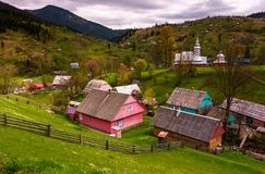 Synevyrs`ka Poliana village in Carpathians. Lovely rural landscape with wooden fences on grassy slopes and a church on hillside among houses. beautiful nature Stock Photo