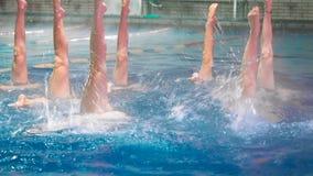 Synkroniseringssimmare lägger benen på ryggen rörelse Spensliga benflickaidrottsman nen att klibba ut ur vattnet i öppen pöl i vi arkivfilmer