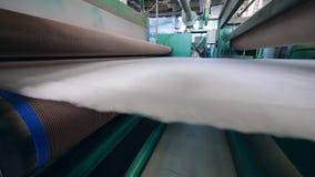 Syntetisk fiber som på flyttar en fabrikslinje med rullar lager videofilmer