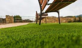 Syntetiskt gräs på parkerar med bänkar på en Pale Sky royaltyfri fotografi